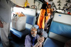 In West Bengal some bauls also earn money busking on trains.  Here two Bauls sing, while an elderly man begs for alms.