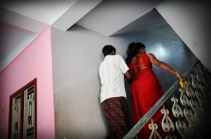 A hijra leads a man up to her room.