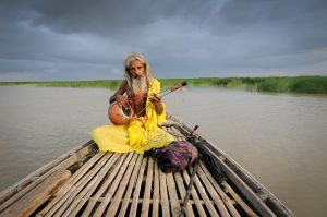 A Baul — member of a religion that worships the human being — traveling down a river in Bangladesh.