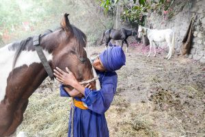 A Sikh boy in the Punjab kisses his horse.