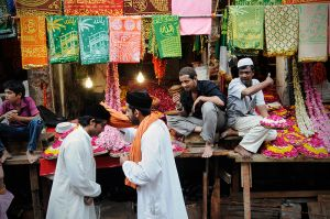 Two Sufis greet each other in Ajmer's bazaar while rose petal vendors call out to pilgrims