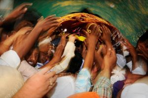 Pilgrims reach to touch a tray of rose petal offerings for the Sufi saint Moin-ud-din Chisti