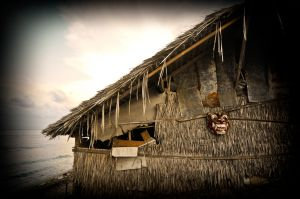 A demon mask hangs on a fisherman's house