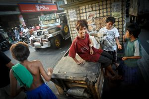 Street kids in Manila play with a homeless dog.  In the background a jeepney is decorated with the words