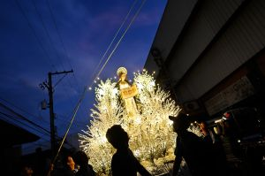 In a Good Friday procession people carry large illuminated decorations commemorating Jesus, Mary and various saints.
