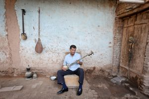 An Uighur man at home plays a traditional instrument.