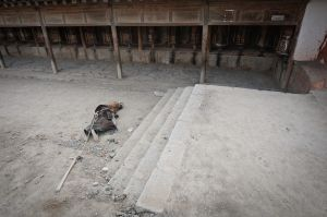 A Tibetan pilgrim prostrates herself in front of a temple.