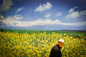 A Chinese Muslim passes a large poster of an imaginary landscape in western China.