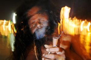 A blind sadhu smokes hashish on the banks of the Ganges