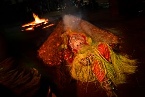 A man possessed by the god of fire rests on a bed of glowing coals.