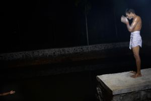 A man prepares for a ritual bath in a water tank prior to dancing in the Padayani.