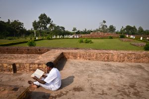 A Sri Lankan pilgrim reads the sutras in the ruins of a temple built on the site where Buddha's house is said to have stood in Jetavana.  The house was called Gandha Kuti or Fragrant Hut, because of the flowers and incense that his devotees used to leave there. True to his principle that not his personality but his teaching should be revered, Sakyamuni always remained wary of excess devotion. The sutras tell that when the offerings made by his devotess became overwhelming, the Buddha gave instructions that a banyan tree, the same kind of tree under which he had gained enlightenment, should be planted nearby. In Buddhism the banyan tree is a symbol of enlightenment, and devotees from then on were instructed to leave their offerings in front of the tree rather than in front of the Buddha's house.