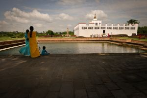Pilgrims in Lumbini Gardens gaze toward a modern temple constructed over the place of the Buddha's birth. Near the temple stands a column erected by the Buddhist Emperor Ashoka in the third century BC.