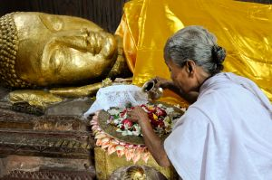 "A pilgrim makes offerings in front of an ancient gilded sculpture of the dying Buddha in Kushinagar near the place where he died, probably in his eightieth year. His last words were reported as follows: ""Decay is inherent in all worldly things. Strive for your own liberation with diligence."""
