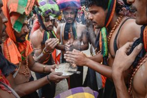 Ritually bathed and cleansed of the paint that covered them at the start of their journey, pilgrims strap bundles of offerings to their heads and sanctify their holy neckalces before setting out for Sabarimala.