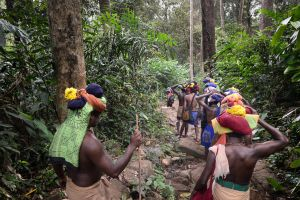 A group of pilgrims bearing offerings strapped to their heads snakes its way through the forest along a sixty kilometer mountain path to Ayyappa's shrine.
