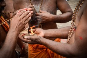 Men sanctify the holy necklace they wear for the duration of the pilgriamge over a sacred flame held by their guruswami. Pilgrims going to Sabarimala follow a strict discipline of restrictions, including a forty-one day vow pledging vegetarianism, celibacy, discipline and humility.