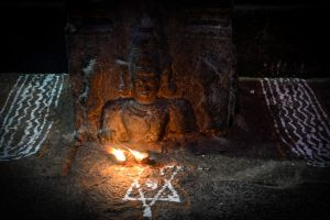 Votive candles in front of a small image of Shiva.