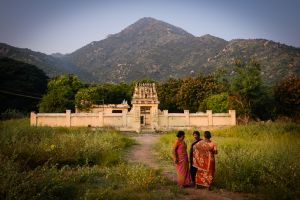 Pilgrims pause in front of a small shrine at the base of Arunachala Mountain. The mountain is an extremely ancient extinct volcano. For one week every year a large fire is ignited on the mountain's summit, and it is believed that the god Shiva manifests himself in this fire.