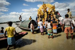 Men load an image of Durga onto a riverboat.