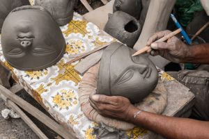 A craftsman sculpting the face of Durga.