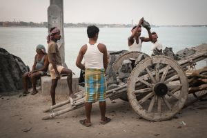 Workmen load river clay onto a cart to deliver it to the nearby idol workshops in Kumartuli.