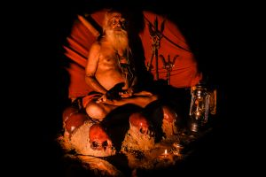 A Tantric sadhu meditates on a seat of human skulls.