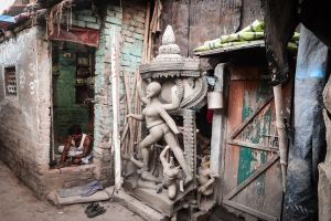 A craftsman in his workshop in Kamurtuli. An unfinished image of Kali sits drying outside.