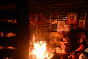 A Tantric practitioner holds offerings to his heart and chants mantras before throwing them into the fire.