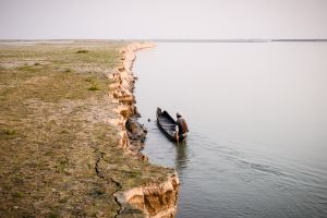 A fisherman in the Brahmaputra River paddles along the crumbling edge of Majuli Island.