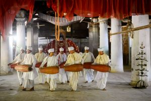 Monks perform sacred music and dance during a ceremony in a temple.