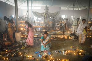 Devotees light candles during a ritual in a temple.