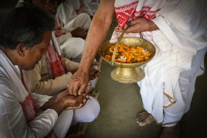 At the conclusion of a ritual a monk distributes sanctified flowers.