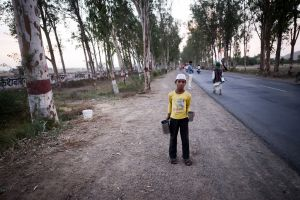 A boy stands at the roadside to offer water to passing pilgrims.