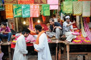 Two Sufis greet each other in Ajmer's bazaar while rose petal vendors call out to passing pilgrims.