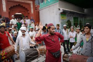 Stopping to rest on their way out of Delhi, pilgrims play music and dance at a Sufi shrine.