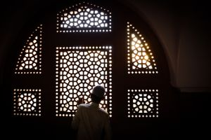 A boy at a shrine in Delhi watches Sufis celebrate the commencement of their pilgrimage.