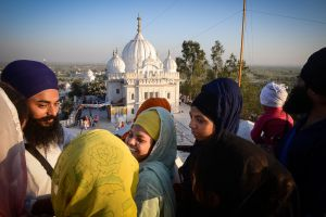 Pilgrims above a Gurudwara, literally the Gateway to the Guru; it is called such because it houses the Sikh book of scriptures, the Guru Granth Sahib, which is venerated as the living physical embodiment of the Guru.