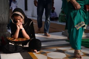 A woman meditates or prays at the Golden Temple.