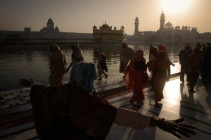 Pilgrims greet the sunrise at the Golden Temple in Amritsar, the Sikhs' holiest site. Sikh Tradition tells that, at the request of the Sikh Guru Arjan, the foundation stone for the temple was laid by the Sufi saint Mian Mir.