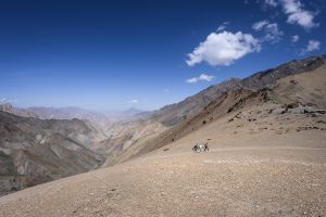 A man and a young girl on a horse cross a high pass in the trans-Himalayan region of India.