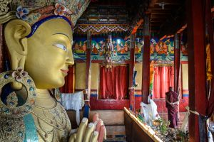 A monk passes a statue of the Buddha Maitreya at the Thikse Monastery in the trans-Himalayan region of Ladakh.