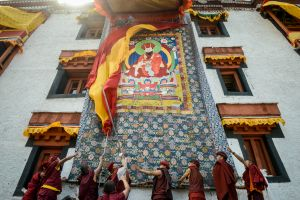 Monks display a giant Thangkha, a religious painting of their guru, on the wall of their monastery during a festival.