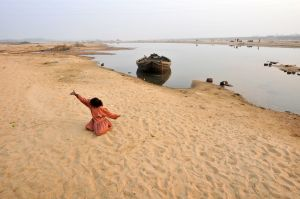 A girl plays in the sand near a river in rural Bengal.