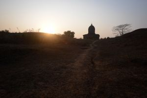 The sun sets behind a medieval temple in rural Bengal.