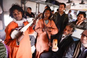 Bauls busk on a train while traveling to the Joydev Mela in Kenduli.