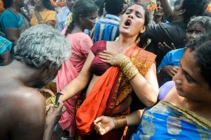 A hijra wails while a priest breaks her bangles.