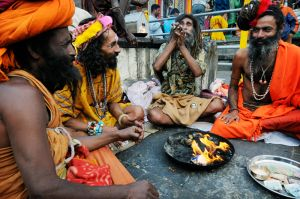Sadhus wait for alms near the entrance to the Kedarnath temple -- warming themselves by a fire, smoking hashish and blessing pilgrims who seek their benediction.